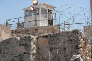 A watch tower sitting over the Palestinian section of Hebron, covered in barbed wire.